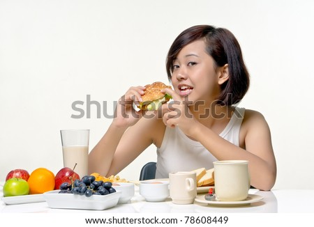 Young pretty teenager ready to bite vegetable burger for morning breakfast, isolated background