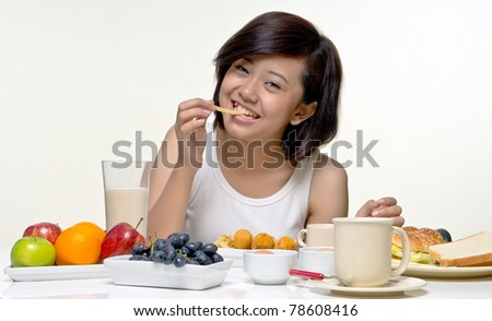 Young pretty teenager smiles while eating fries for morning breakfast, isolated background - stock photo