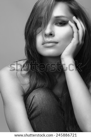 Young pretty topless woman sitting on gray background