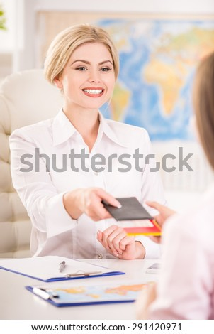 Young pretty travel agent giving tickets to clients. - stock photo