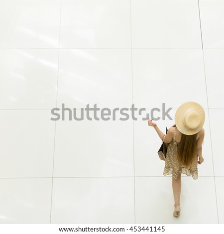 Young pretty traveler woman walking in the shopping centre carrying shopping bag over left hand wearing dress and a hat. View from above, rear view, copy space, square shot