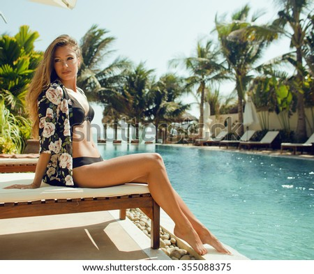 young pretty woman at swimming pool relaxing in chair, fashion look lingerie at hotel close up smiling cool vacations summer - stock photo