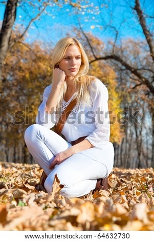Young pretty woman at the autumn colored park .