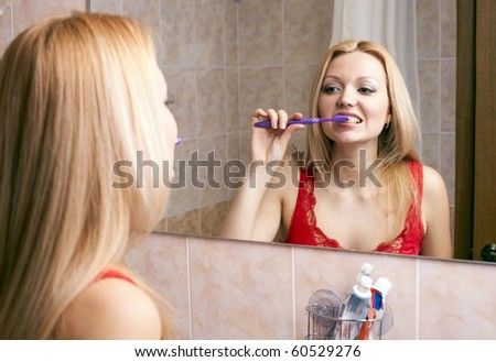 Young pretty woman brushing her teeth - stock photo