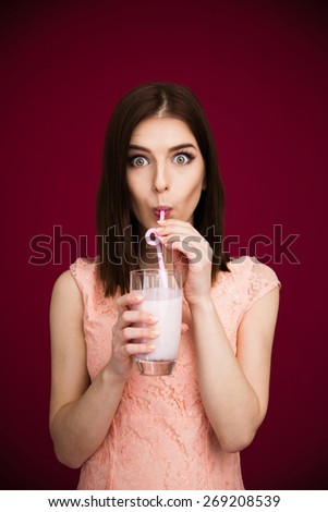 Young pretty woman drinking yogurt over pink background and looking at camera - stock photo