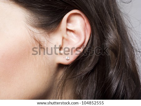 Young pretty woman ear closeup - stock photo