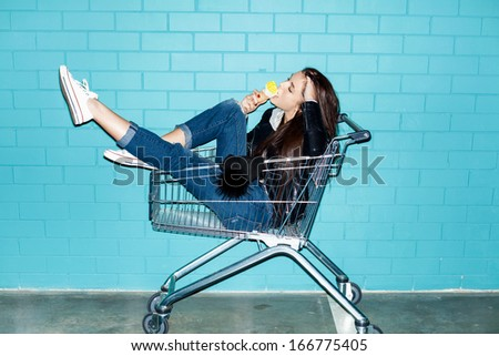Young pretty woman eating ice cream over blue brick wall. Naughty girl having fun in shopping cart. Indoors, lifestyle - stock photo