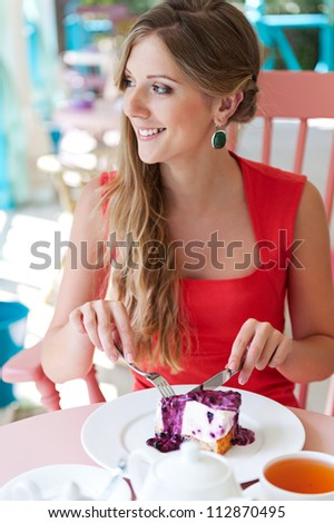 young pretty woman eating tasty cake and smiling - stock photo