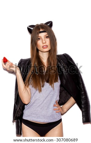Young pretty woman enjoy fresh strawberries. Girl with bright makeup and hairstyle with cat ears, on white background, not isolated - stock photo