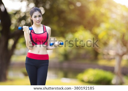 Young Pretty woman exercises by using small dumbbell with blurred green park background - stock photo