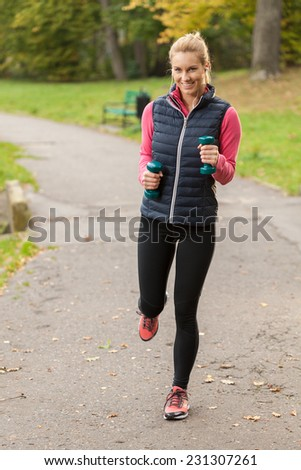 Young pretty woman exercising with dumbbells in park - stock photo