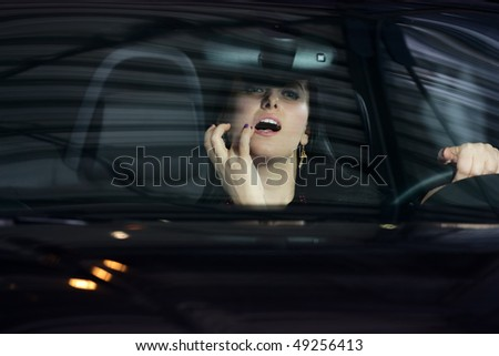 young pretty woman going over her lips with a lipstick - stock photo