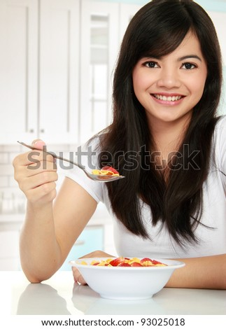 young pretty woman having a bowl of cereal for her breakfast - stock photo