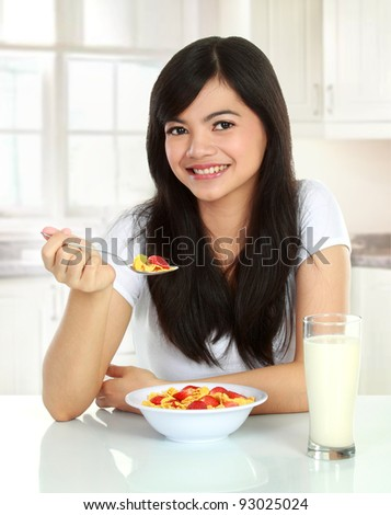 young pretty woman having a bowl of cereal with milk for her breakfast - stock photo