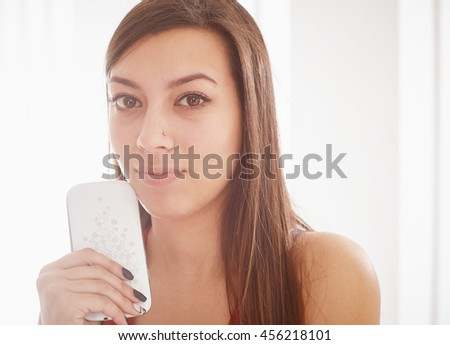 Young pretty woman holding a mobile phone and looking away. Close up picture.