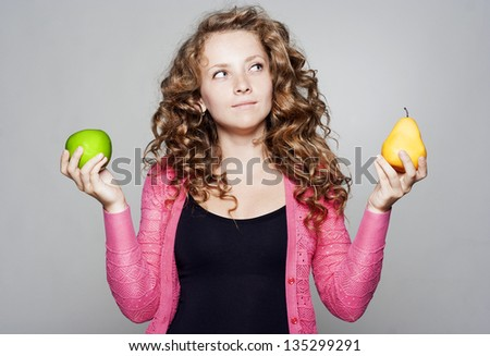 Young pretty woman holding an apple and a pear - stock photo