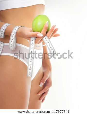Young pretty woman holding apple and measure tape - stock photo
