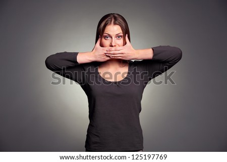 young pretty woman holding hands over her mouth over grey background - stock photo