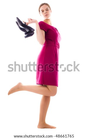 Young pretty woman holding her shoes in a hand. She's looking arrogant and vain. White Background.