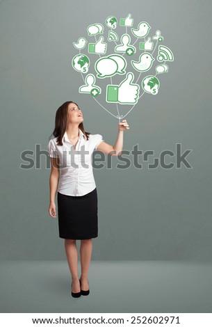 Young pretty woman holding social icon balloon - stock photo