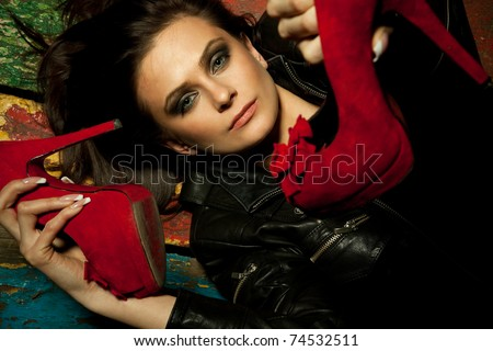 Young pretty woman holds red shoes with hands
