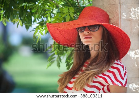 Young pretty woman in a red hat - stock photo