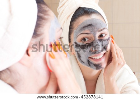 Young pretty woman in bathrobe and with towel on head removing facial mask in front of mirror in bathroom. Skin care and beauty concept - stock photo