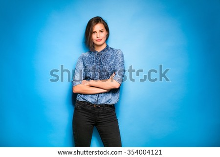 young pretty woman in blue shirt standing confident on blue background - stock photo