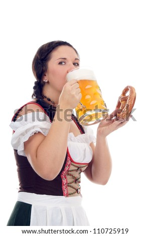 young pretty woman in dirndl with beer and pretzels / munich beer fetival - stock photo