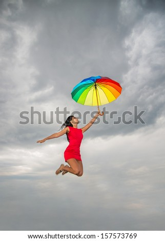 Young pretty woman in red dress jumping with rainbow umbrella against overcast sky - stock photo