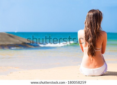 young pretty woman in sunglasses in white bikini sitting on tropical beach with lighthouse in background