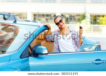 Young pretty woman in sunglasses standing near convertible with keys in hand - concept of buying a used car or a rental car