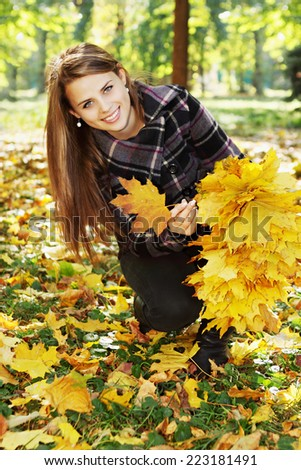 Young pretty woman in the autumn park makes a wreath of leaves - stock photo