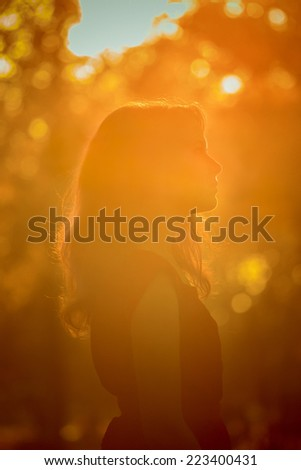 Young pretty woman  in the autumn park profile  view backlit by sunset headshot - stock photo
