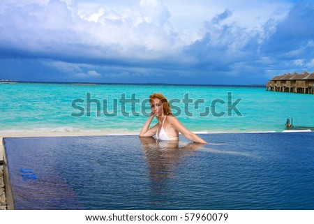 Young pretty woman in the pool and ocean in the background. Maldives - stock photo