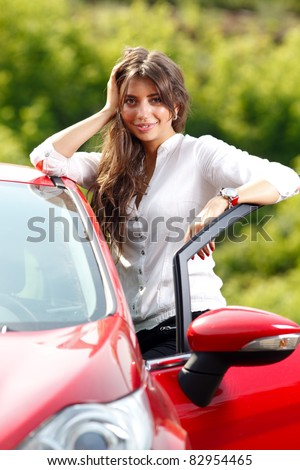 Young pretty woman in the red car - stock photo