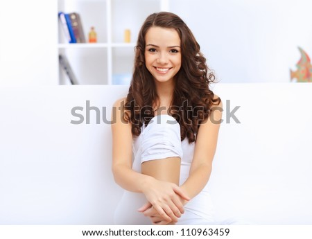 Young pretty woman in white at home sitting on the sofa - stock photo