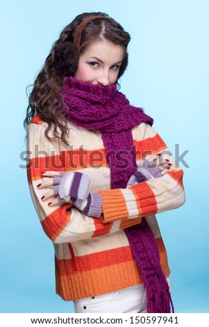 Young pretty woman in winter dress on blue background - stock photo