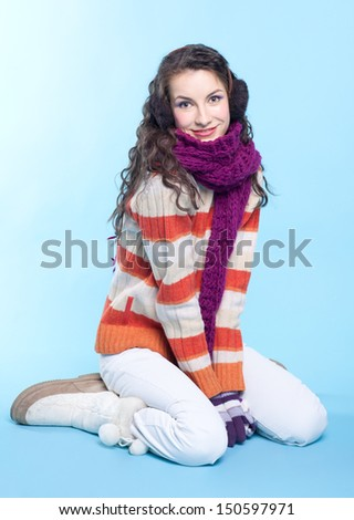 Young pretty woman in winter dress sitting on blue background - stock photo