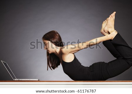 Young pretty woman in yoga bow posture looking at laptop, backlit grey background. - stock photo