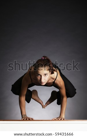 Young pretty woman in yoga crow posture (bakasana), backlit on grey background, front view. - stock photo