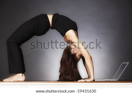 Young pretty woman in yoga wheel posture looking at laptop, backlit grey background. - stock photo