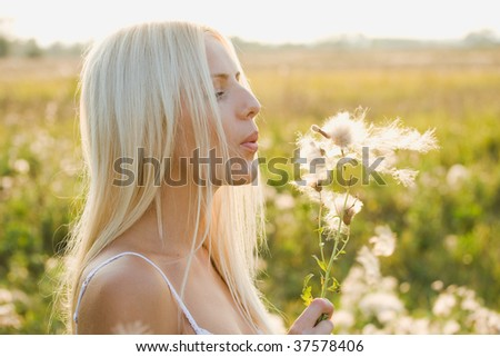 Young pretty woman is blowing to dandelion - stock photo