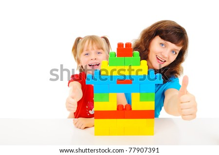 Young pretty woman is playing with her daughter - stock photo