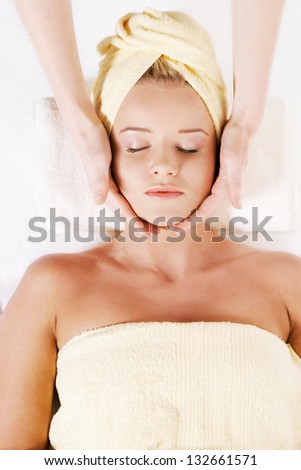 Young pretty woman laying down and receiving face massage - stock photo