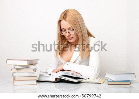 Young pretty woman learning at table with a lot of books, educational concept - stock photo
