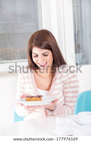 young pretty woman looking sweet dessert on the table with smile - stock photo