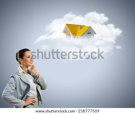 Young pretty woman looking thoughtful at cottage model - stock photo