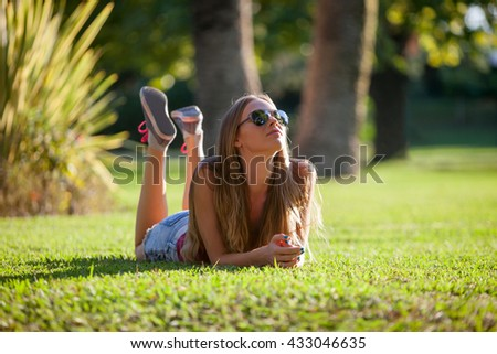 Young pretty woman lying and relaxing on a grass - stock photo
