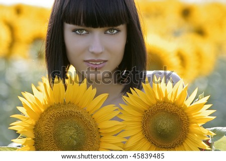 Young pretty woman on a field of sunflowers background - stock photo